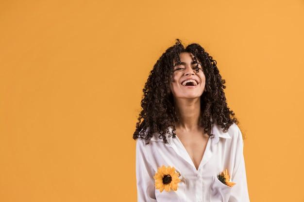Mujer negra con flores en bolsillos de camisa riendo.