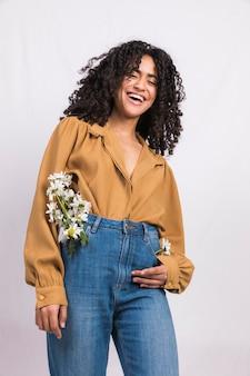 Mujer negra con flores de margarita en bolsillo de jeans riendo