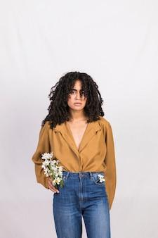 Mujer negra con flores de margarita en el bolsillo de los pantalones vaqueros