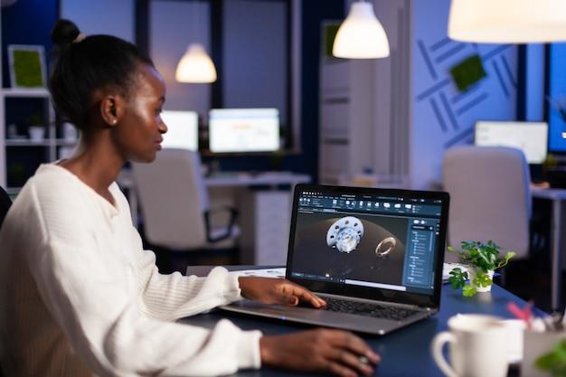 Mujer negra en la industria mecánica trabajando a altas horas de la noche haciendo horas extraordinarias en la oficina de puesta en marcha