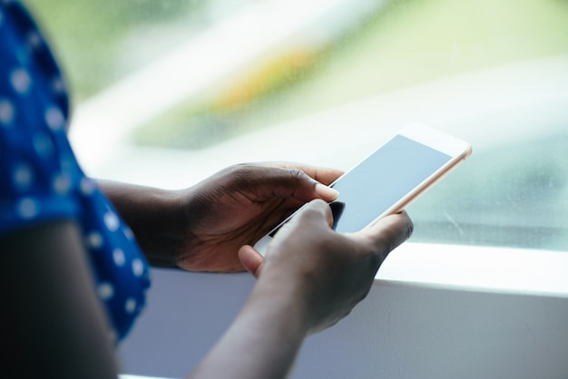 Mujer negra irreconocible con smartphone