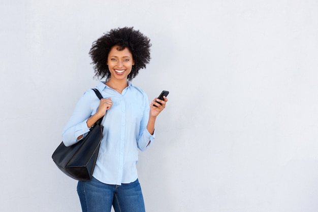 Mujer negra joven confiada que sostiene el teléfono móvil y que sonríe en el fondo blanco