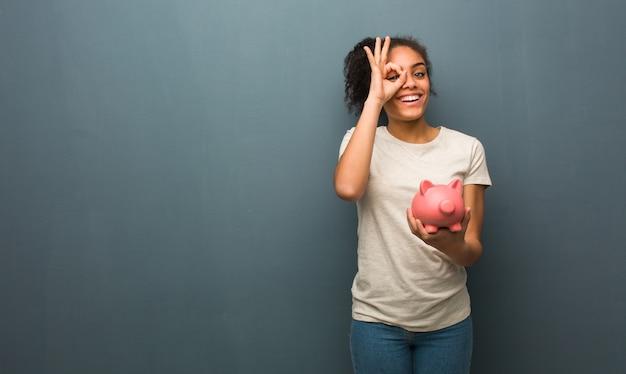 Mujer negra joven confidente que hace gesto aceptable en ojo. ella está sosteniendo una alcancía.