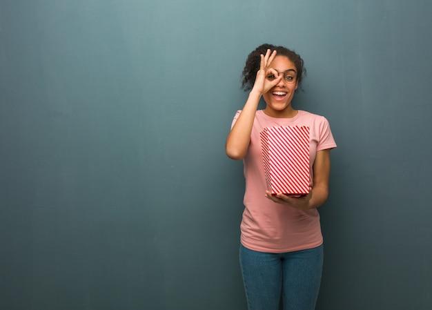 Mujer negra joven confidente que hace gesto aceptable en ojo. ella está sosteniendo un cubo de palomitas de maíz.