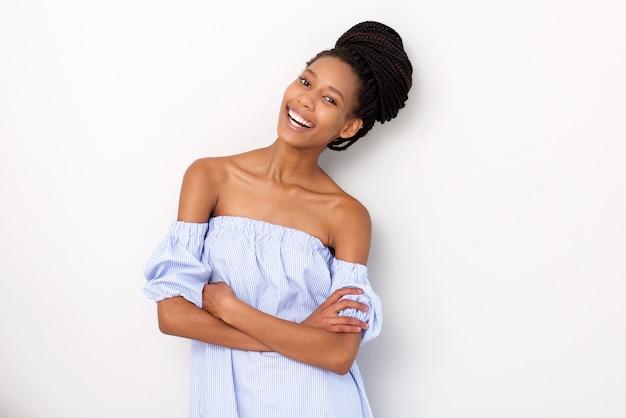 Mujer negra joven elegante que ríe contra el fondo blanco