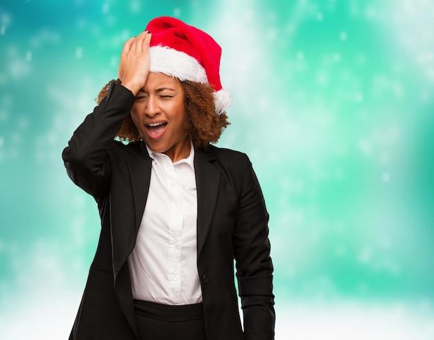 La mujer negra joven del negocio que lleva un sombrero de santa de chirstmas olvidadizo, realiza algo