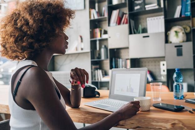 Mujer negra joven que mira el ordenador portátil y que se sienta en oficina moderna del co-trabajo