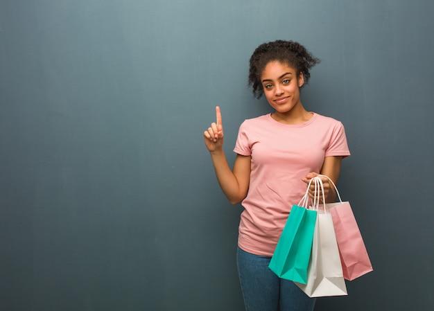 Mujer negra joven que muestra el número uno. ella está sosteniendo una bolsas de compras.