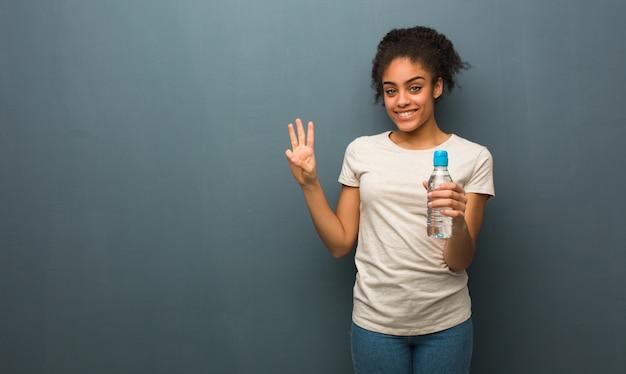 Mujer negra joven que muestra el número tres. ella está sosteniendo una botella de agua.