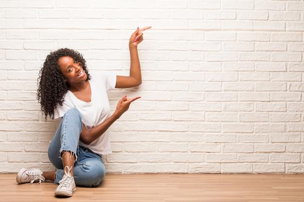 Mujer negra joven que se sienta en un piso de madera que señala al lado