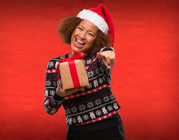 Mujer negra joven que sostiene un regalo en el día de navidad alegre y que sonríe