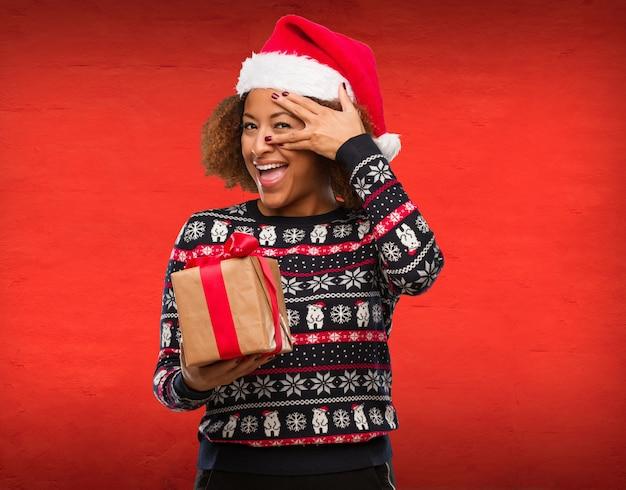 Mujer negra joven que sostiene un regalo en el día de navidad avergonzado y que ríe al mismo tiempo