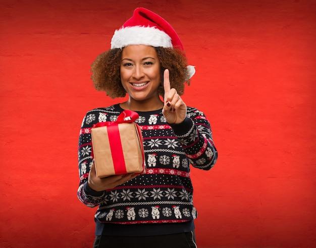 Mujer negra joven que sostiene un regalo en el día de la navidad que muestra el número uno