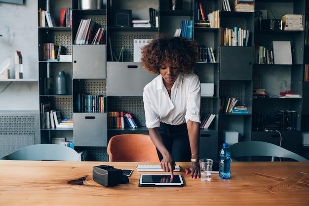 Mujer negra joven que usa la tableta en oficina moderna