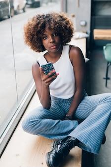 Mujer negra joven con el smartphone que mira la cámara