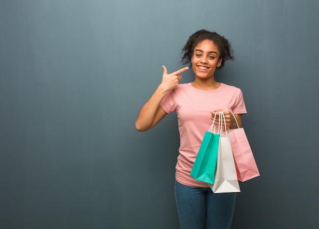 La mujer negra joven sonríe, señalando la boca. ella está sosteniendo una bolsa de compras.