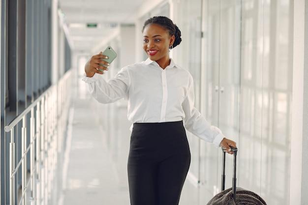 Mujer negra con maleta en el aeropuerto