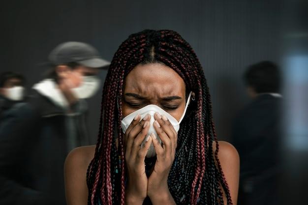 Mujer negra con una máscara y tosiendo en una concurrida