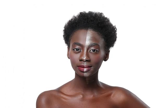 Mujer negra con media cara en maquillaje, concepto de belleza