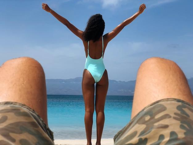 Mujer negra mirando a otro lado en la playa con los brazos abiertos