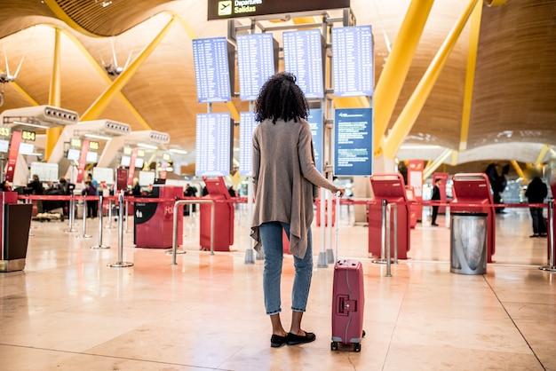 Mujer negra mirando el panel de información de horarios en el aeropuerto con una maleta