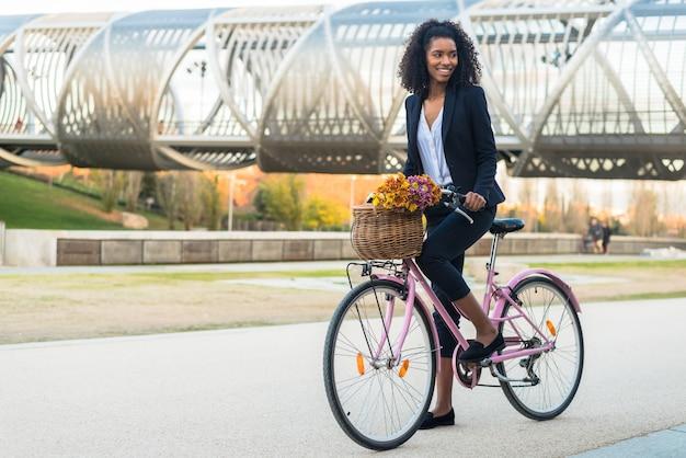Mujer negra de negocios andar en bicicleta vintage en la ciudad