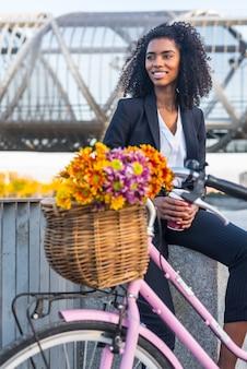 Mujer negra de negocios con bicicleta vintage bebiendo café