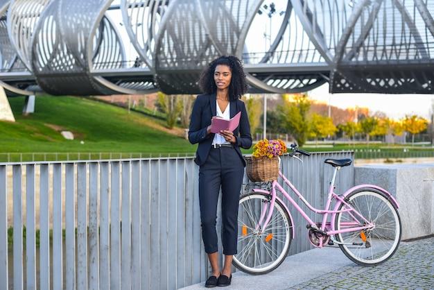 Mujer negra de negocios con bicicleta vintage junto al río mirando su agenda