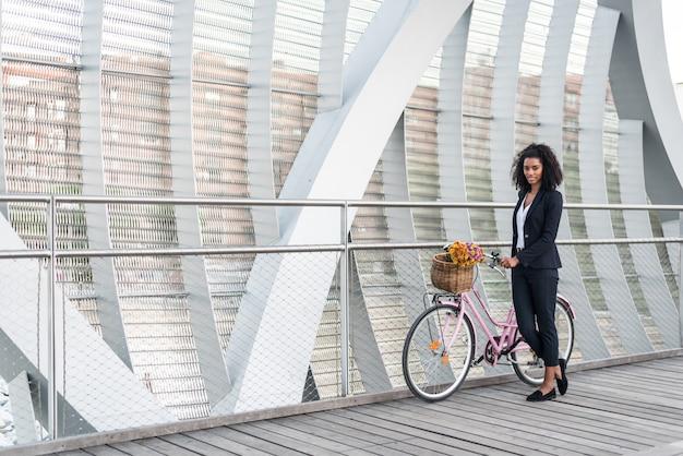 Mujer negra de negocios con bicicleta vintage en un puente