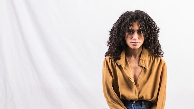Mujer negra pensativa en camisa con estilo