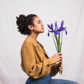 Mujer negra pensativa que sostiene la flor azul