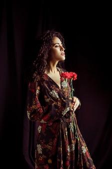 Mujer negra pensativa que sostiene las flores del clavel