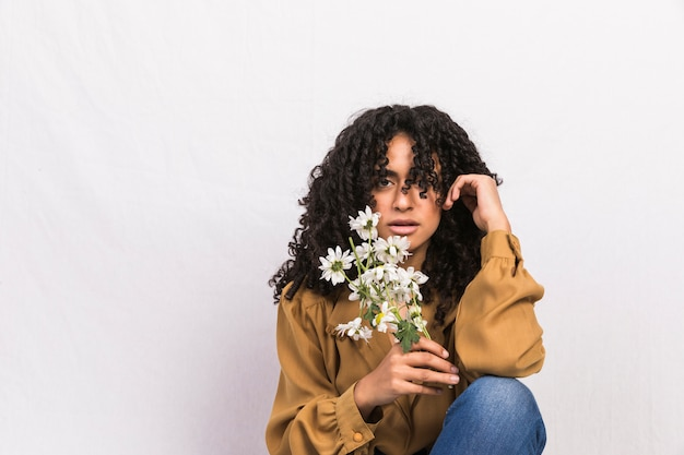 Mujer negra pensativa que sostiene las flores de la margarita