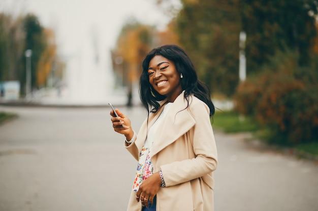 Mujer negra de pie en una ciudad de otoño