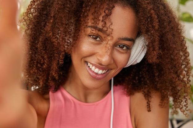 Mujer negra positiva escucha lista de reproducción favorita con auriculares