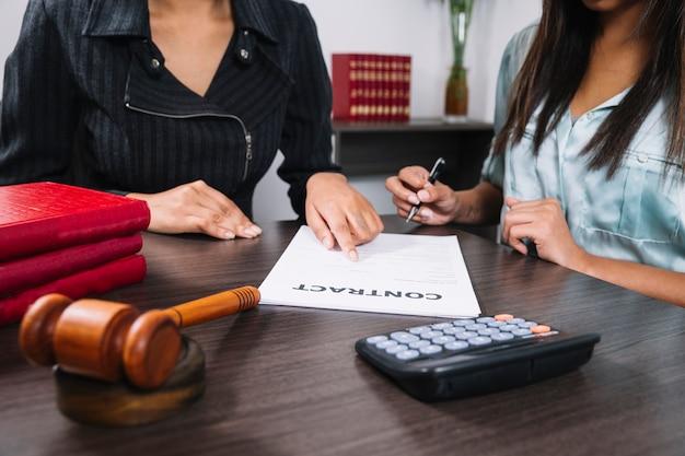Mujer negra que señala en el documento cerca de la dama con la pluma en la mesa con calculadora y martillo
