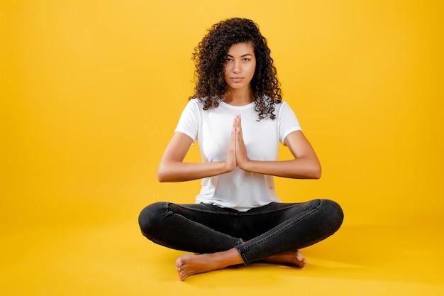 Mujer negra relajada meditando en pose de yoga aislado sobre amarillo