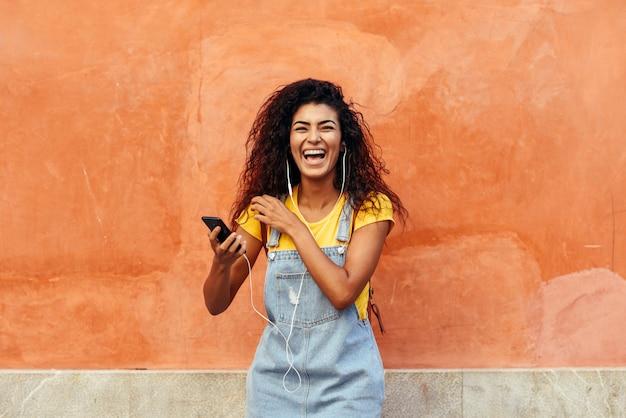 Mujer negra riendo y escuchando música con auriculares.