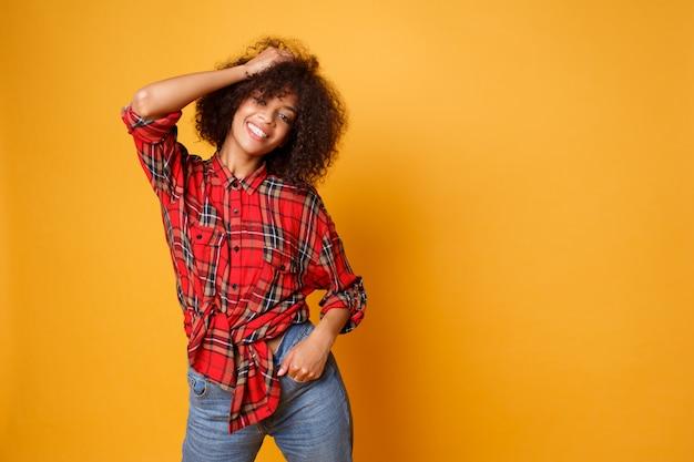 Mujer negra de risa optimista que presenta en estudio en fondo anaranjado. modelo femenino rizado relajado disfrutando de la vida.