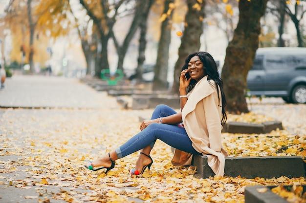 Mujer negra sentada en una ciudad de otoño