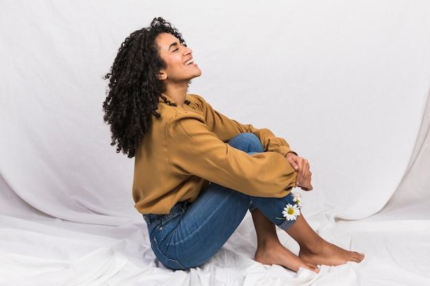 Mujer negra sentada con flores de margarita en puños de jeans