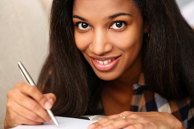 La mujer negra sonriente escribe historia en cuaderno