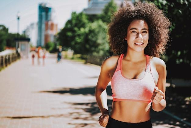 Mujer negra sonriente en el parque. estilo de vida activo y saludable.