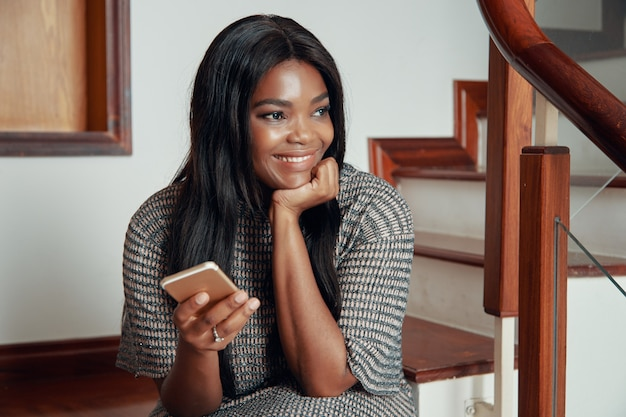 Mujer negra sonriente que se sienta con el teléfono en las escaleras