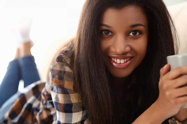 La mujer negra sostiene la taza sus sonrisas de la mano