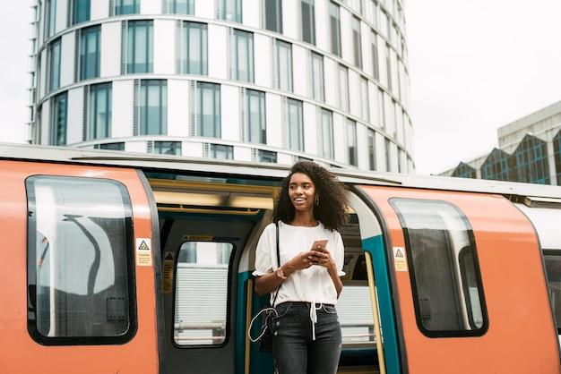 Mujer negra con teléfono móvil en el metro de londres