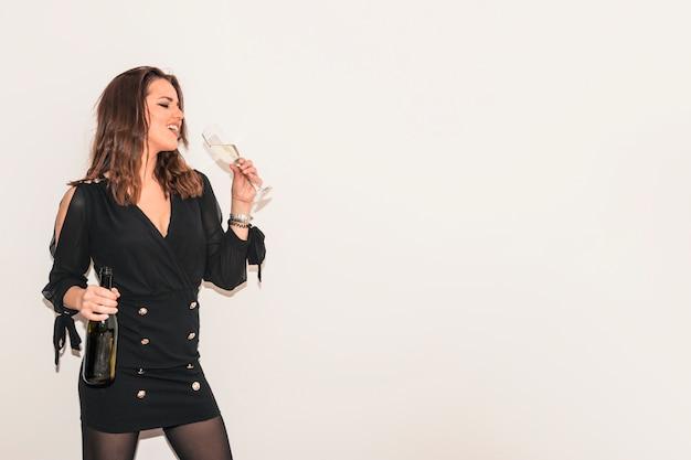 Mujer en negro bebiendo champán de vidrio