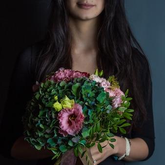 Una mujer de negro con un ramo de flores verdes en la mano sobre un fondo de estudio