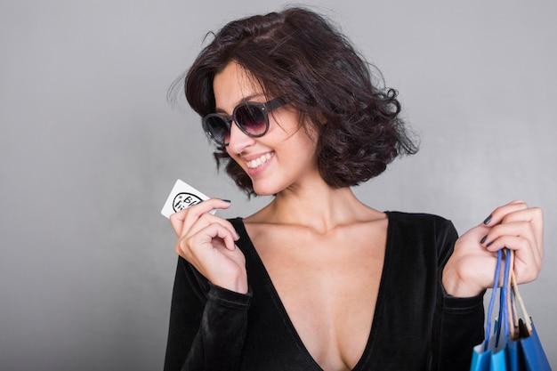 Mujer de negro con tarjeta de crédito.