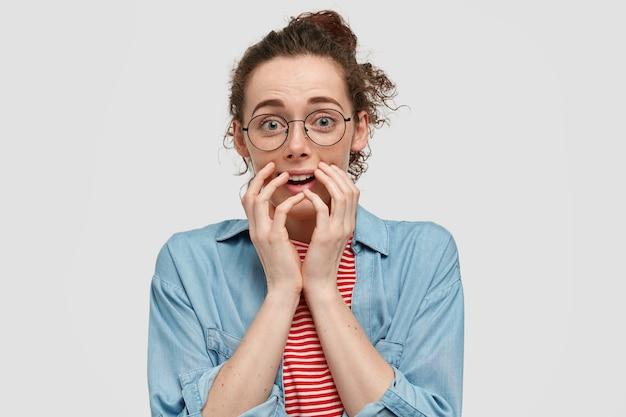Mujer nerviosa avergonzada con piel pecosa, mantiene las manos cerca de la boca, mira nerviosamente, está complacida con algo agradable, usa gafas redondas, aisladas sobre una pared blanca. emociones, reacción